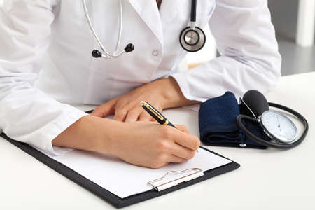 Doctor writing down notes about patients examination