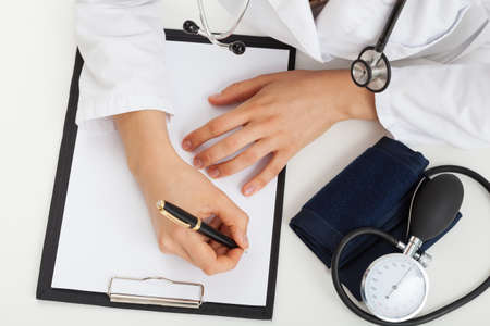 doctor's office: Doctor is writing a medical report