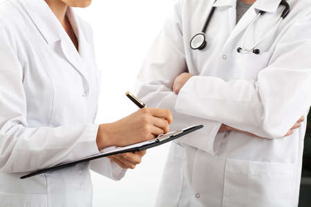 Young female doctor taking notes about patient's treatment photo