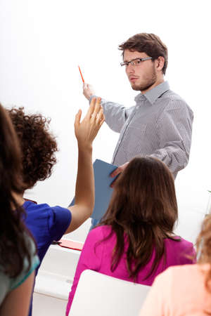 lecturer: Young lecturer discussing with group of students during the classes Stock Photo