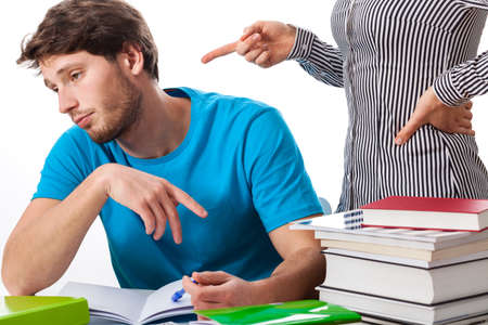angry teacher: Angry teacher warning a lazy student to study more  Stock Photo