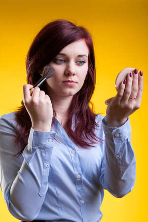 Woman getting ready to work, applying powder with brush photo