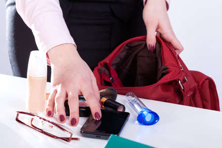 stuff: Woman packing personal stuff to her handbag