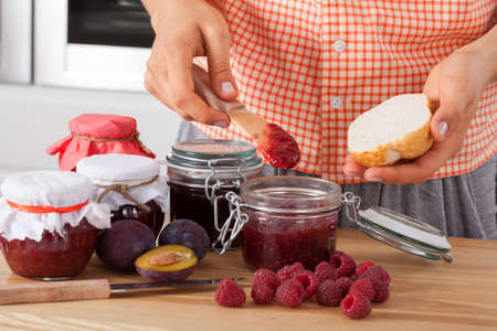 Woman tasting fresh homemade raspberry jam photo