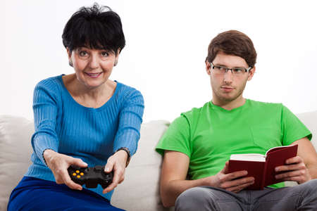 Elderly woman is playing video game while her son is reading a book photo