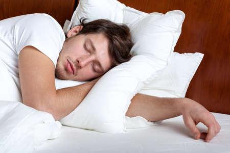 Yong homem dormindo em sua cama no travesseiro branco