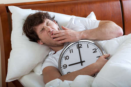 morning routine: Man holding a big clock and waking up Stock Photo