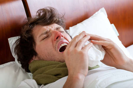 Man having a cold sneeze in his bed photo