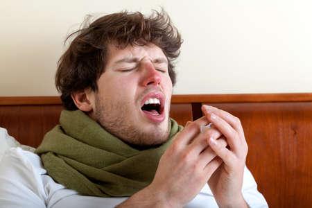 부비동 감염이 침대에서 재채기를 가진 남자 스톡 콘텐츠