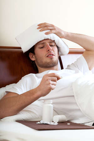 Man with migraine lying in bed and taking pill photo