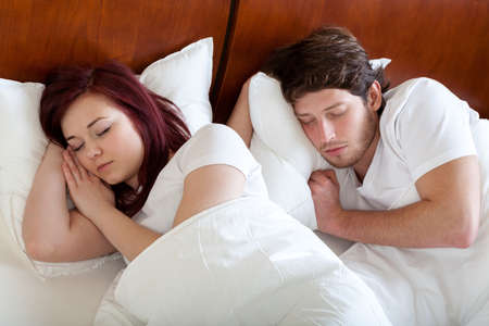 Couple sleeping peacefully under the  white duvet photo