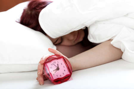 snooze: Woman trying to turn of alarm clock