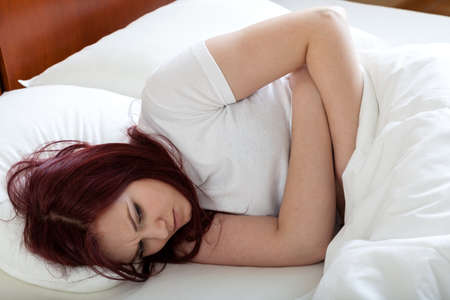 Upset woman lying in bed beacuse of stomachache