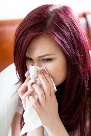 Woman sitting on her bed and blowing nose photo