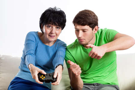 Grandson teaching how to play video games his grandma photo