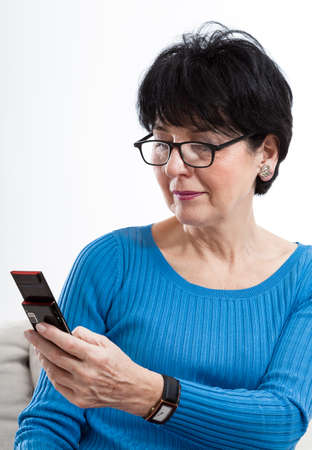 Elder woman wearing glasses and using smartphone photo