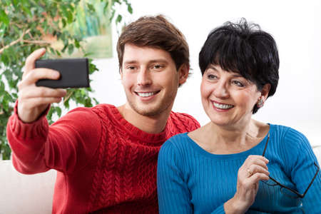 Son taking a selfie with his mother by using a smatphone photo