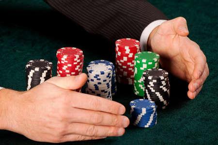 fichas casino: Un primer plano de un hombre que toma montones de coloridas fichas de casino