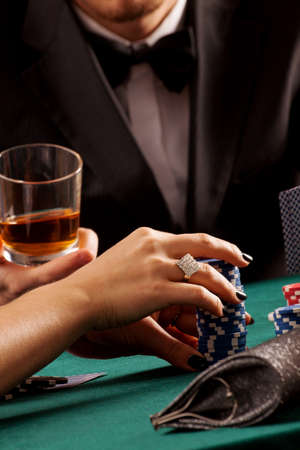 piling: A womans hand piling casino chips on a table