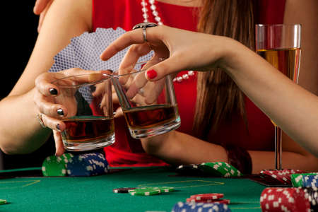 proposing a toast: Women proposing a whiskey toast while in a casino