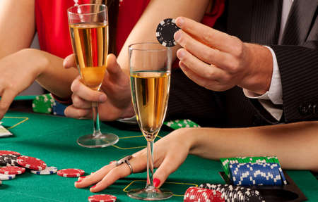 Gamblers holding casino chips and glasses of champagne photo
