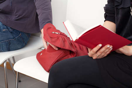 sneaky: A sneaky thief trying to steal a bag of a woman sitting next to him Stock Photo