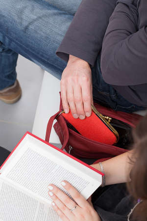 pickpocket: A thief taking a purse out of a womans reading a book bag Stock Photo