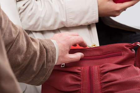 Thief trying to take out the wallet from ladys purse photo