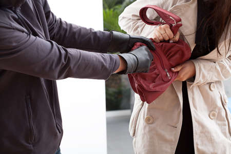 sneaky: A woman trying not to let a man take her bag Stock Photo