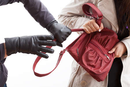 espionage: A closeup of a thief wearing gloves holding a womans bag Stock Photo