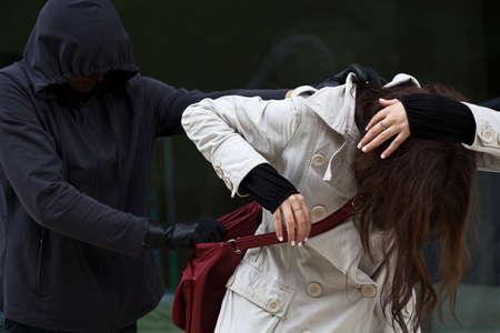 彼女の財布を盗むために望んでいる盗賊に襲われる女性 写真素材