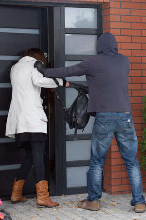 attempting: A robber attempting to break into a womans house Stock Photo