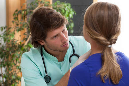 Concerned doctor during examining his patients thyroid Stock Photo