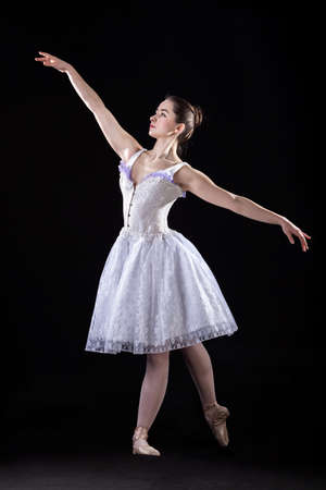Woman dancing ballet on stage, wearing pointes photo