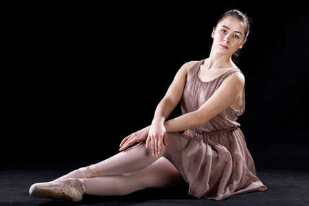 Ballet dancer sitting with grace on a stage photo