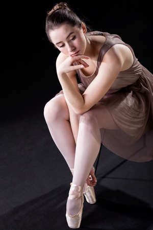 Ballet dancer sitting and  thinking before performance photo