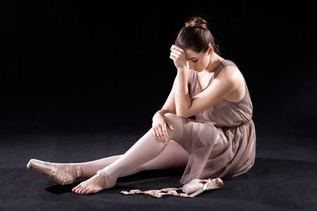 discouraged: Frustrated, discouraged  ballet dancer with tired feet