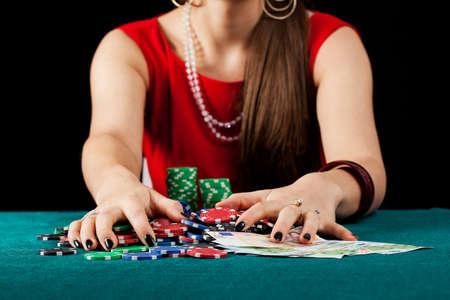 gambler: An elegant female gambler taking chips and banknotes