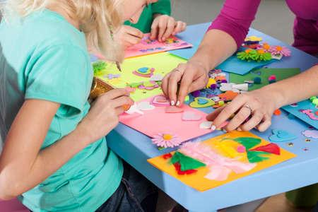 paper craft: Niños que hacen decoraciones de papel de colores con la maestra de arte Foto de archivo
