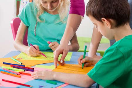 아이들은 미술 교사와 함께 그림을 그리며 창의력을 발달시킵니다.