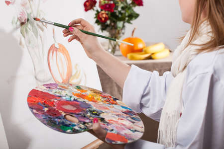 painting: Young talented woman painting a nature on white canvas Stock Photo