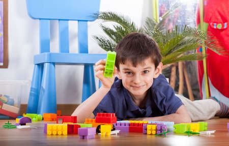 childcare: Small cute boy enjoy playing colorful blocks and smiling Stock Photo