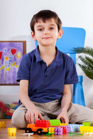 Little cute boy sitting in his room and playing blocks Stock Photo - 25624861