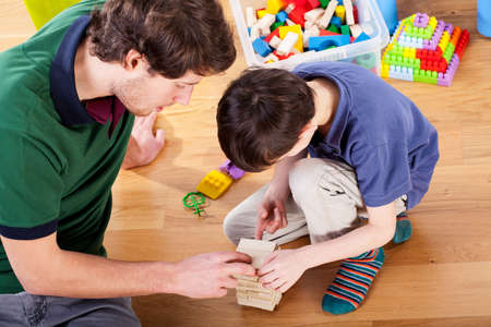 Young good daddy playing toys with his son at home Stock Photo - 25624863