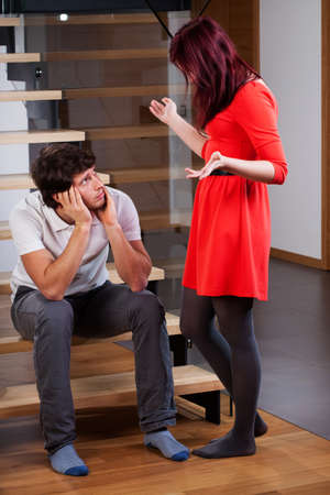 Angry woman standing by bored husband and moaning Stock Photo - 25624869