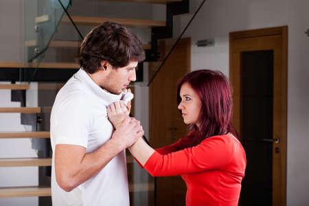 violencia intrafamiliar: Mujer enojada usar la violencia para su pareja durante la pelea Foto de archivo