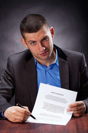 Crook holding an agreement and showing a place for signing Stock Photo - 25626860