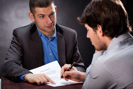 Dishonest businessman convincing his client to sign a contract Stock Photo - 25626861