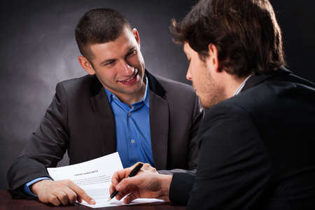 Naive man signing the usury contract with crook