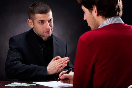 Moneylender convincing client to sign usury contract Stock Photo - 25626868